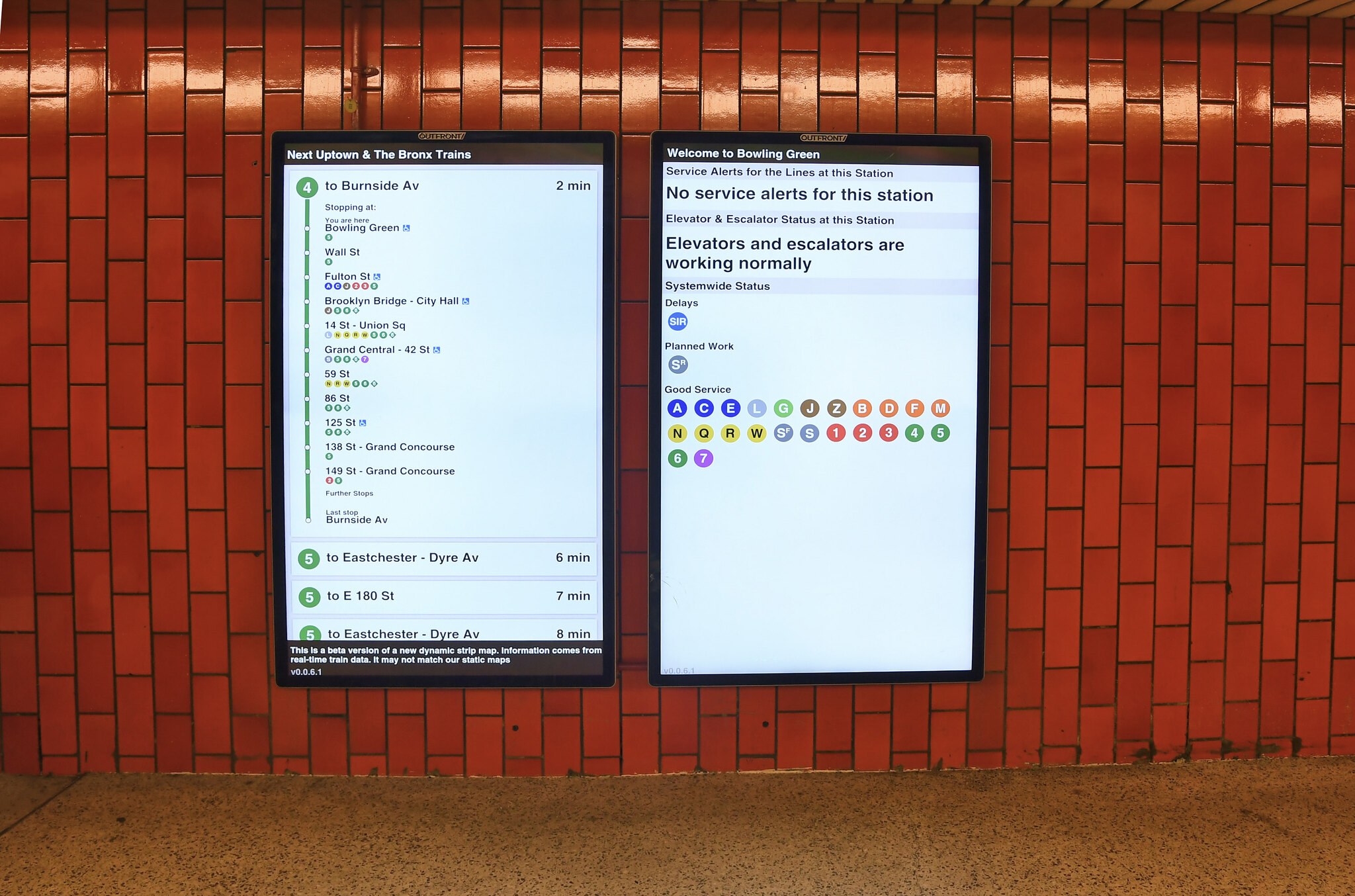 Two digital screens in the subway mounted over red tile. Screens show stop information and system status