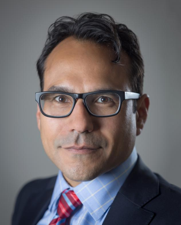 A head shot of Robert Mujica Jr., who looks straight at the camera wearing glasses.