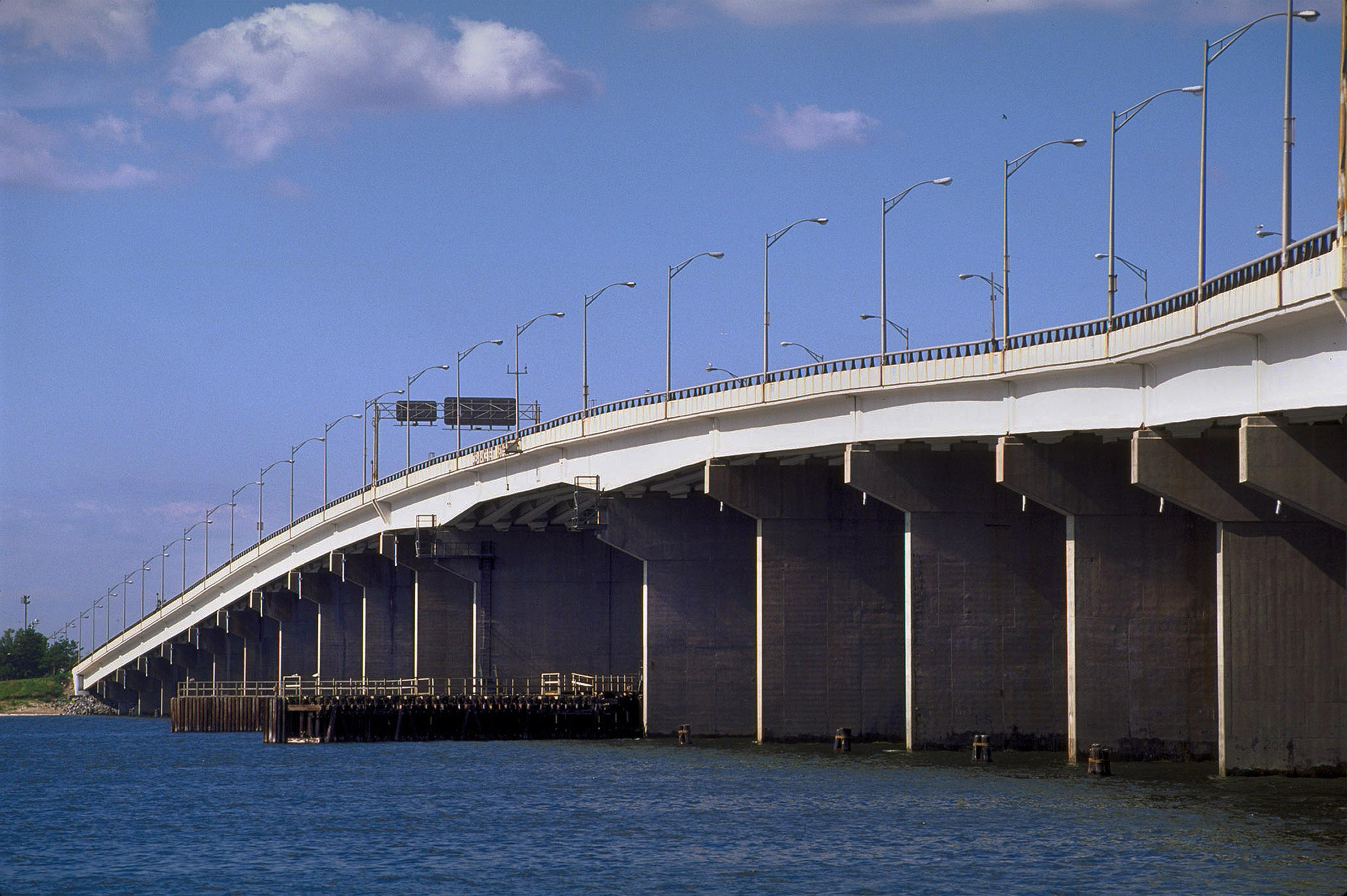 A bridge with traffic signs and streetlights visible stretches across a body of water, with blue sky and clouds overhead.