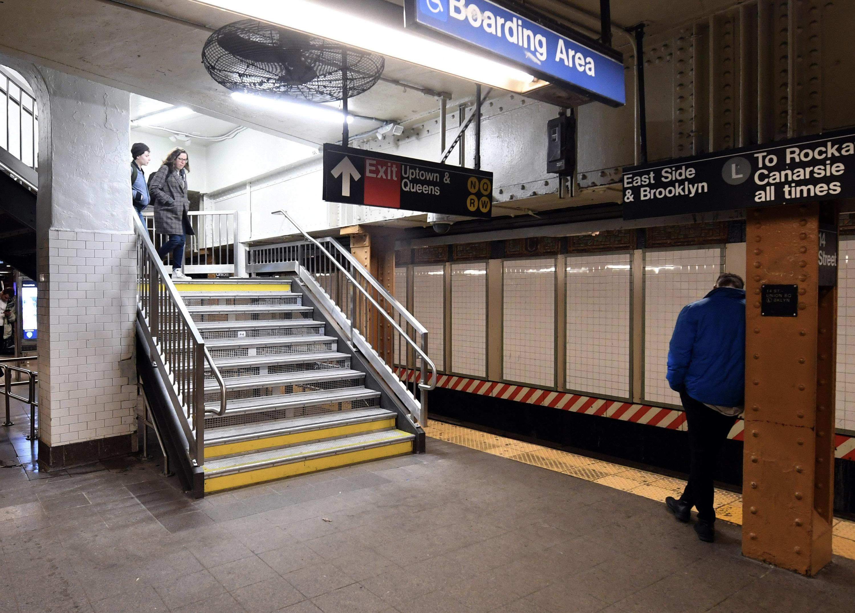 A man leans against a column on a subway station platform as two women walk down the stairs to his left. Several signs are visible, including one for trains on the current platform, one for a wheelchair boarding area, and one for an exit and other train lines.