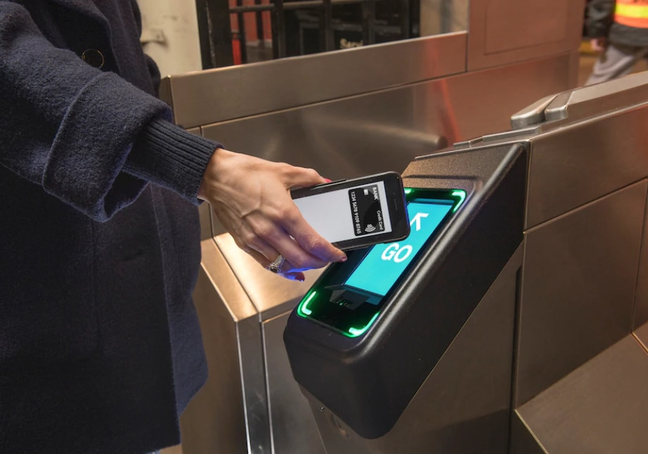 A person holds an iPhone up to a small display on a subway turnstile. The display is flashing green and saying Go.
