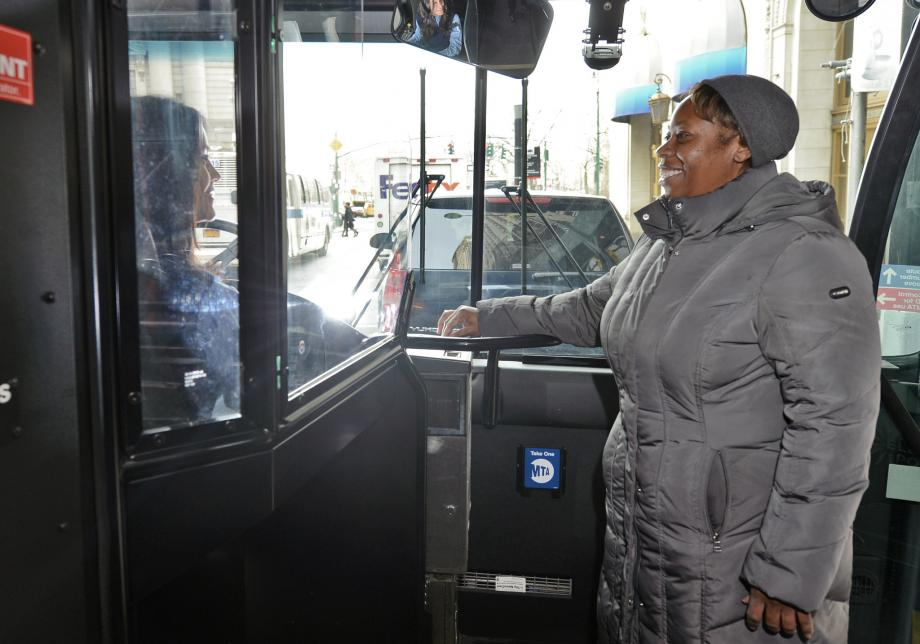 A woman wearing a coat and hat smiles at a bus operator as she inserts her MetroCard into the farebox at the front of a bus.