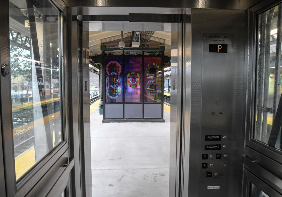 From inside the cab of the platform elevator, a photo of the platform and newly installed glass artwork at Astoria Blvd station.