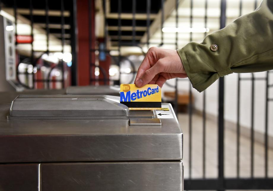 A closeup of someone swiping a MetroCard at a turnstile. The blue and gold MetroCard logo is facing toward the camera and the person swiping it, with the black barcode visible at the bottom.