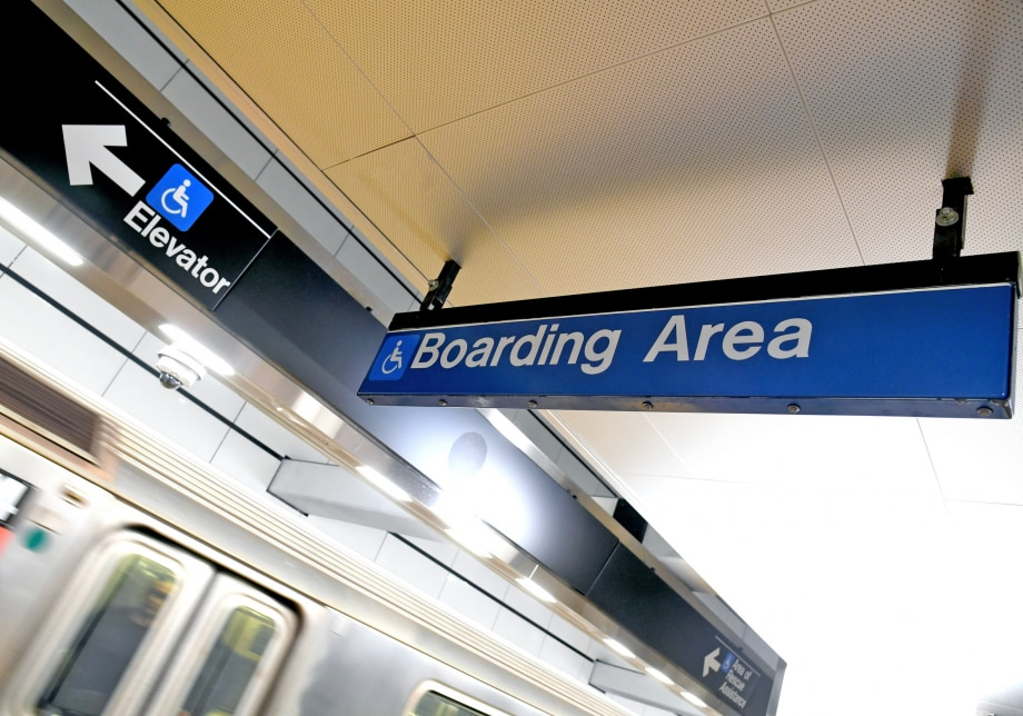 "A blue sign with the words ""Boarding area"" and an icon showing a person in a wheelchair. On a different sign on the left is the same icon and an arrow pointing toward elevators."