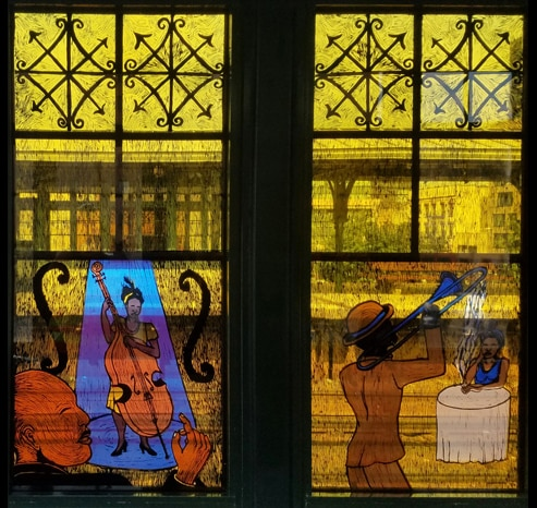 Another stained glass scene shows two musicians, one with an upright bass and one with a trumpet, playing for people sitting at small tables. One woman is listening with her hand on her cheek. A man in a suit is snapping his fingers.