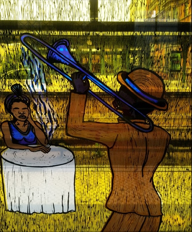 A stained glass scene shows a man in gold playing a blue trumpet while a woman listens at a small table nearby.