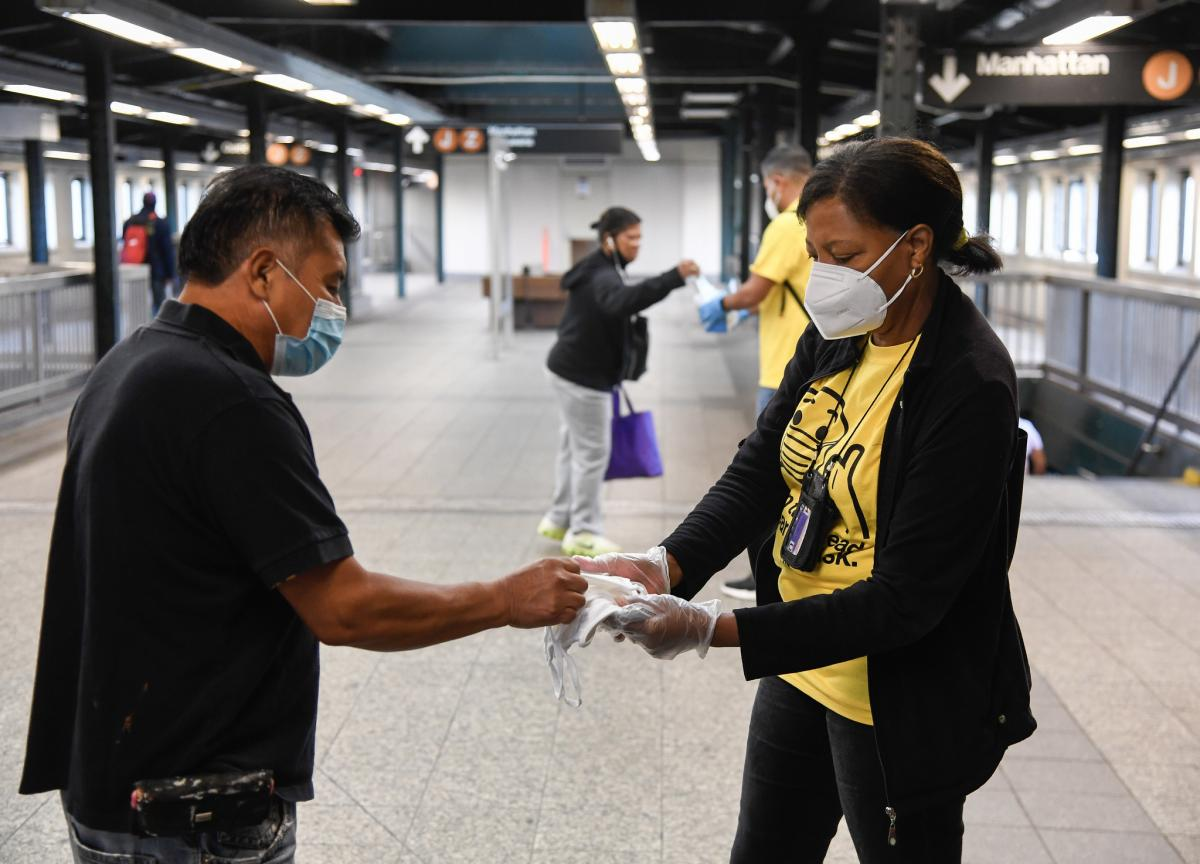 Volunteer wearing yellow shirt offering white cloth masks inside subway stations
