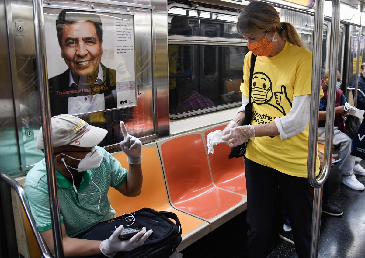 Volunteer distributing masks to a customer on the subway.