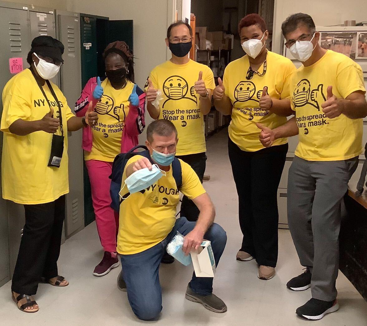 Volunteers in yellow t-shirts and masks giving thumbs up before they head out.