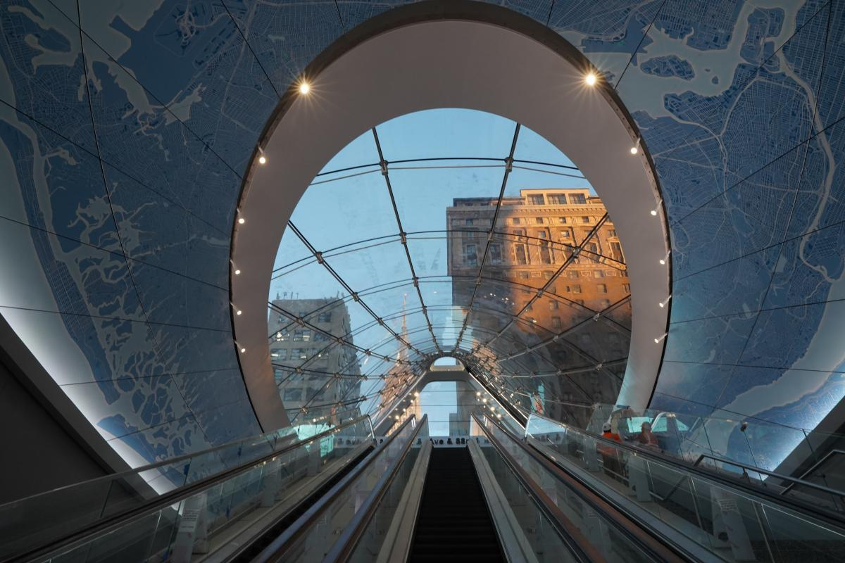 A view from the bottom of an escalator. An ornate ceiling with large windows shows sky and buildings outside.