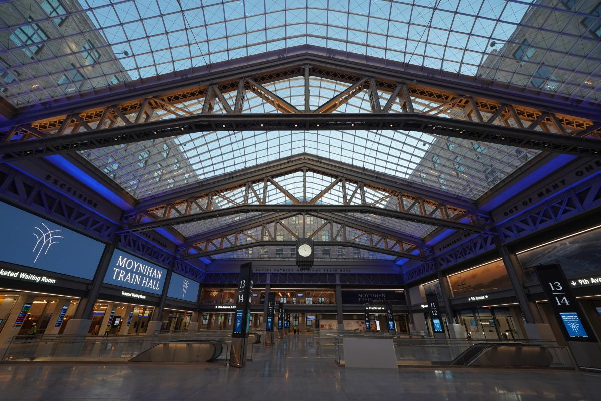 The inside of the train hall, featuring shiny floors and a vaulted glass ceiling. A few people in construction vests are visible in the background.