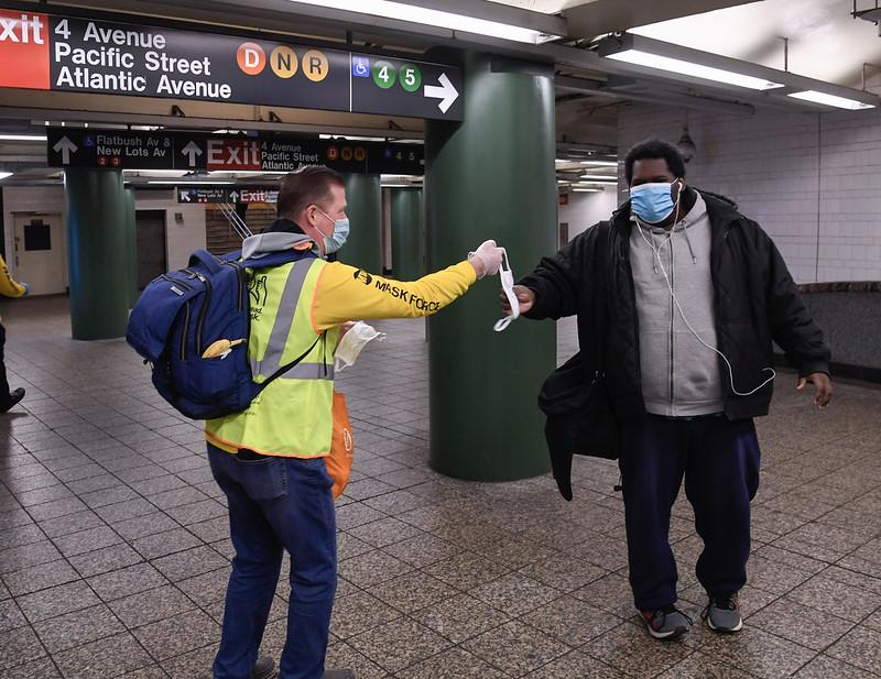 Mask Force volunteer in yellow vest and shirt hands mask to customer walking through Atlantic Av-Barclays station, in the fishbowl