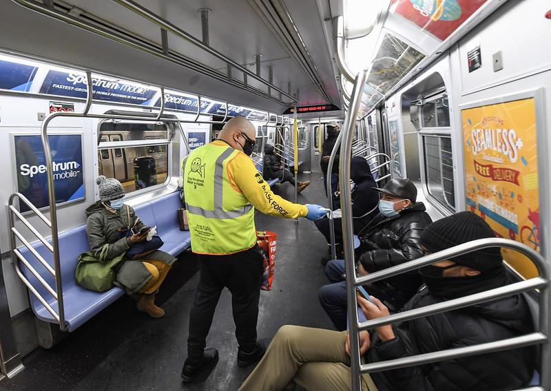 Volunteer in yellow vest and shirt hands mask to customer seated on subway train