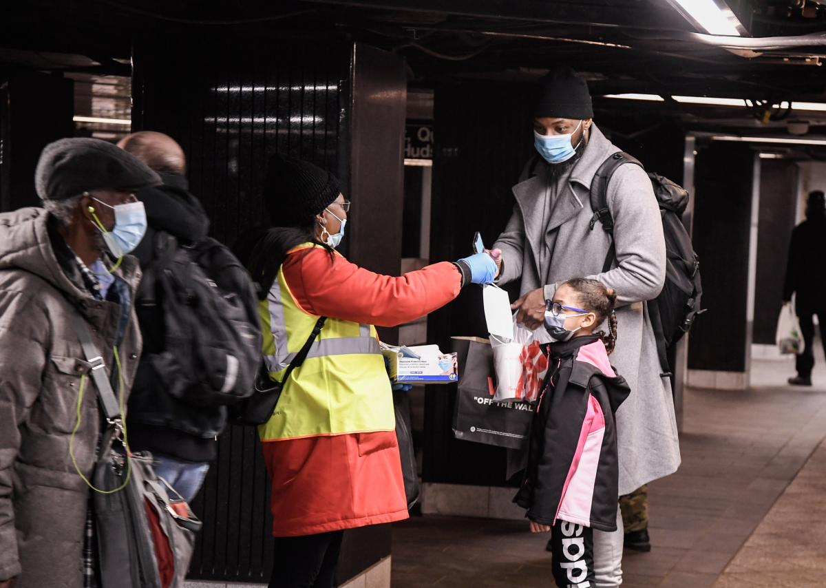 Volunteer in yellow vest and red coat hands mask to tall customer in trench coat and child in back and pink coat.
