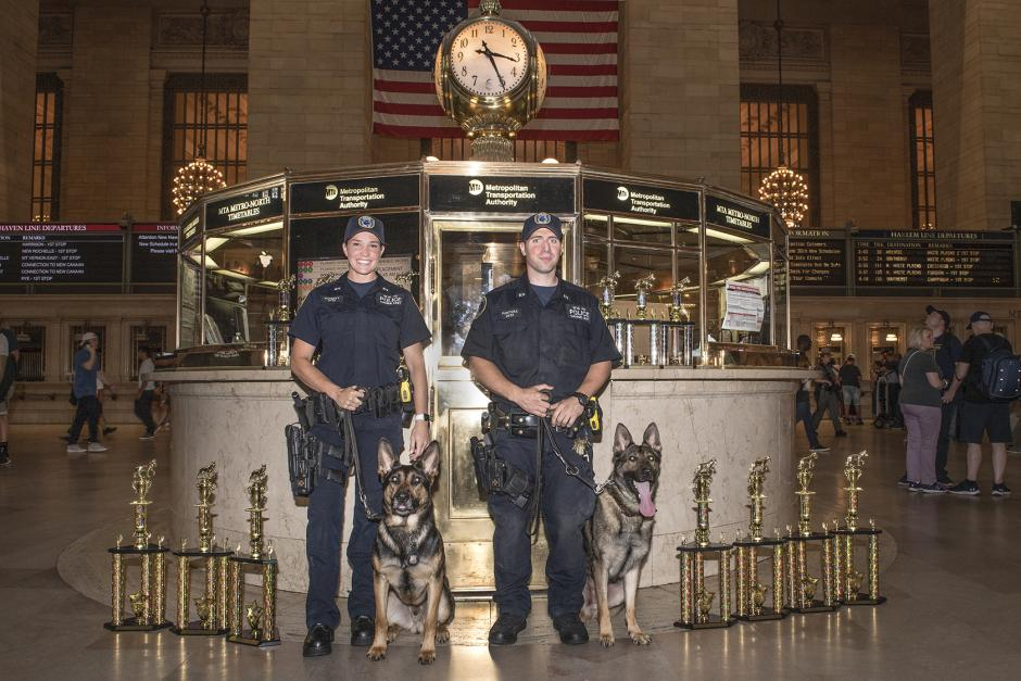 A female and male police officer stand with their K9 partners in front of the information booth at Grand Central Terminal. One of the dogs is sticking its tongue out.