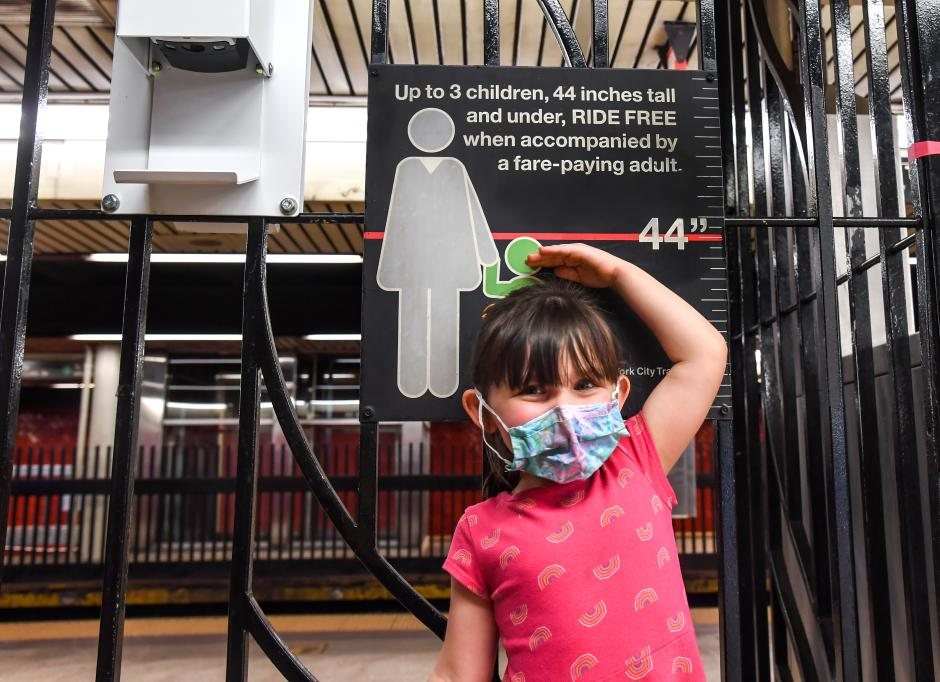 "A young girl stands near a sign saying, ""Up to 3 children, 44 inches tall and under, ride free when accompanied by a fare-paying adult."" She's holding her hand near the line measuring 44 inches, which is above her head."