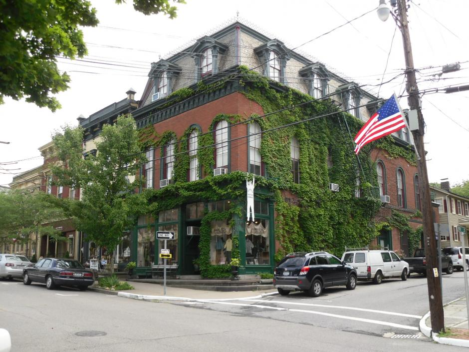 An old-fashioned-looking brick building on the corner of a street in a small downtown area. Greenery covers most of the building's surface, framing arched and gabled windows. An American flag is visible in the foreground.